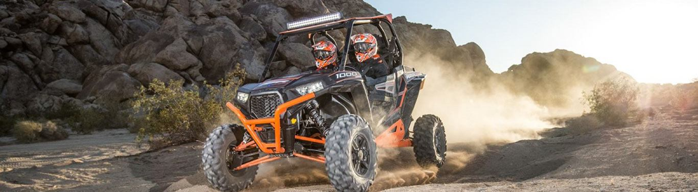 Two riders ride a UTV across a rocky landscape.